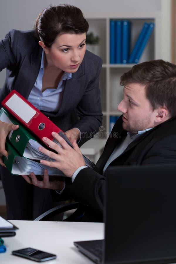 Overworked employee and cruel boss. Image of overworked employee and cruel boss royalty free stock photo