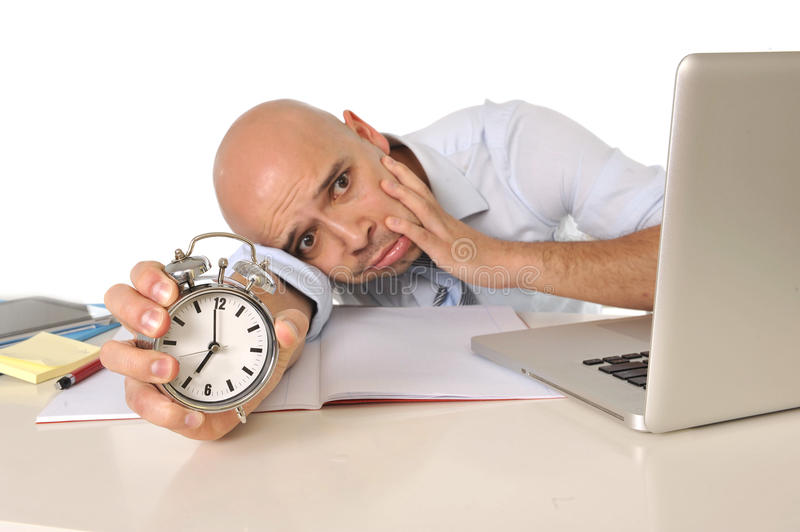 Overworked exhausted bald business man with computer and alarm clock. Overworked exhausted businessman with laptop and alarm clock working extra hours at office royalty free stock photography
