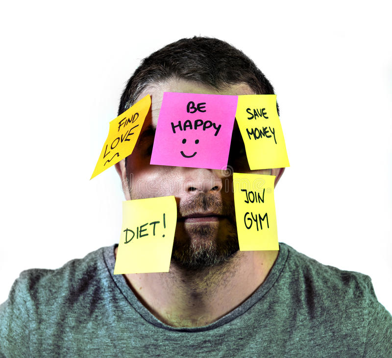 Overworked man in stress with face full of post it notes covering him with reminders and resolutions. Young man overwhelmed and overworked in stress with face royalty free stock photography