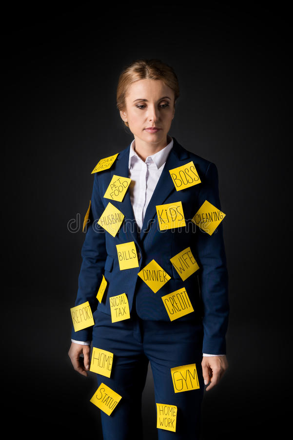 Overworked middle aged businesswoman standing with sticky notes on suit stock photography