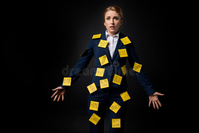 Overworked middle aged businesswoman standing with sticky notes on suit stock image