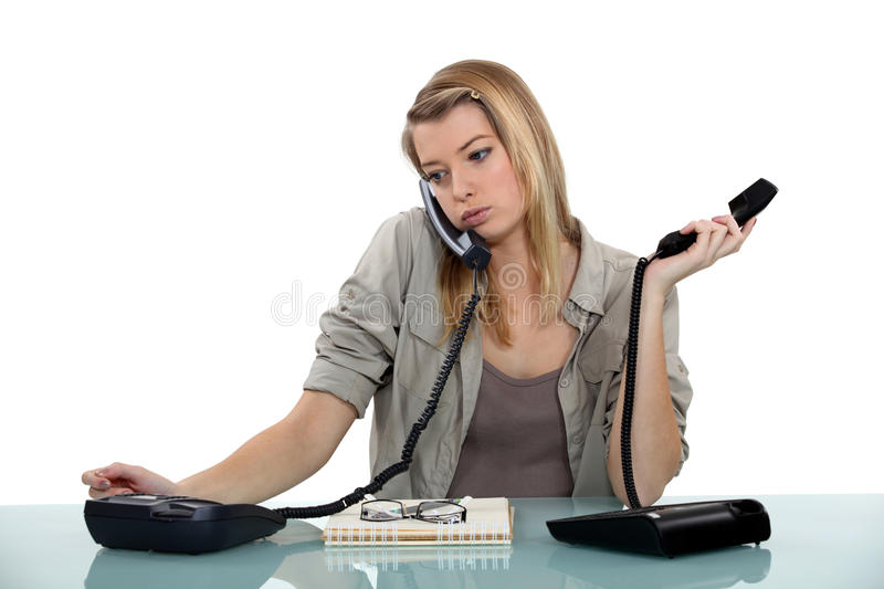 Overworked receptionist. A verworked receptionist young woman royalty free stock image