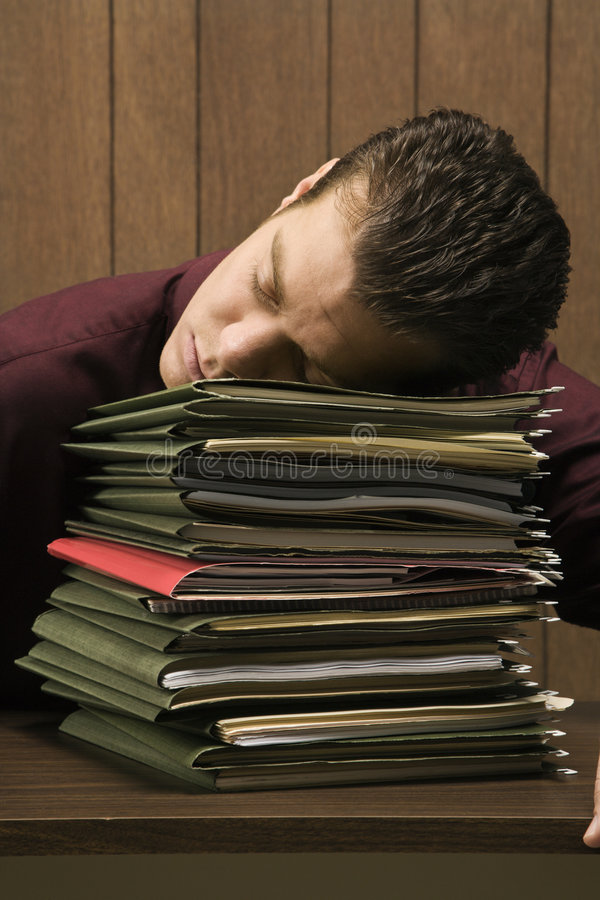 Overworked retro businessman sleeping at desk. Caucasion mid-adult retro businessman sitting at desk with head down sleeping on a tall stack of folders royalty free stock photos