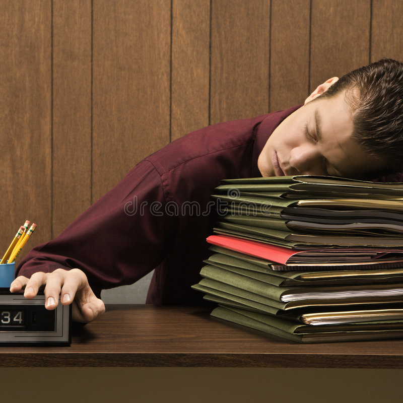 Overworked retro businessman sleeping at desk. Caucasion mid-adult retro businessman sitting at desk with head down sleeping on a tall stack of folders stock photos