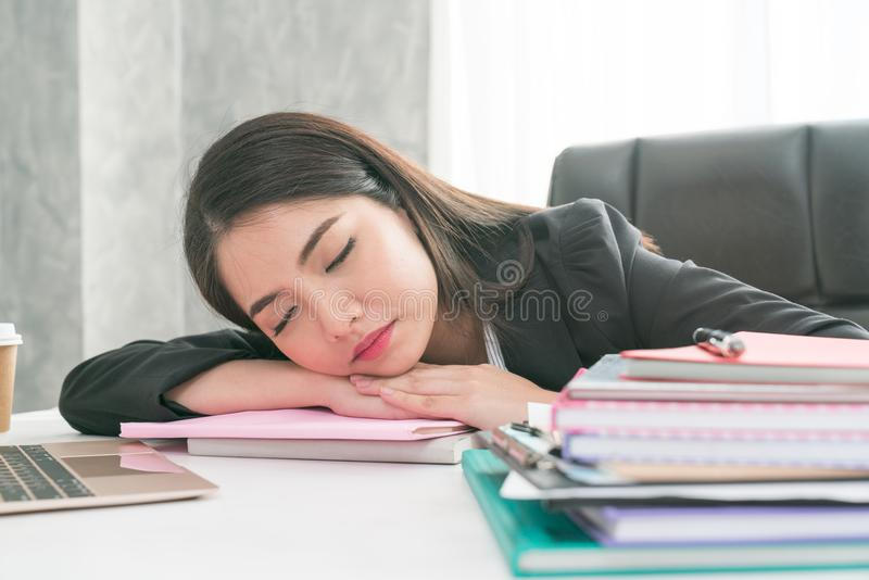 Overworked and tired businesswoman sleeping over a laptop in a d stock photography