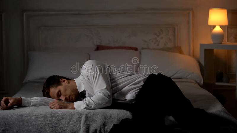 Overworked tired man in suit lying down on bed in exhaustion, single workaholic. Stock photo stock images