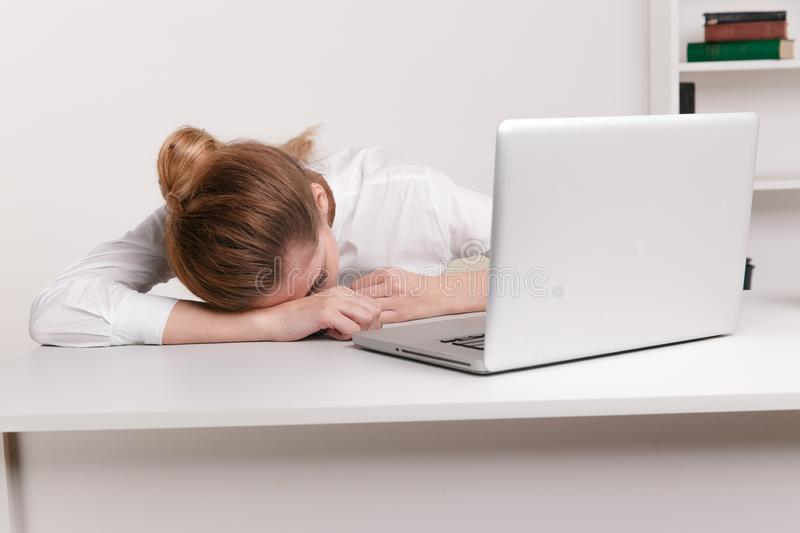 Overworked and tired sleeping over a laptop in a desk at work in her stock image