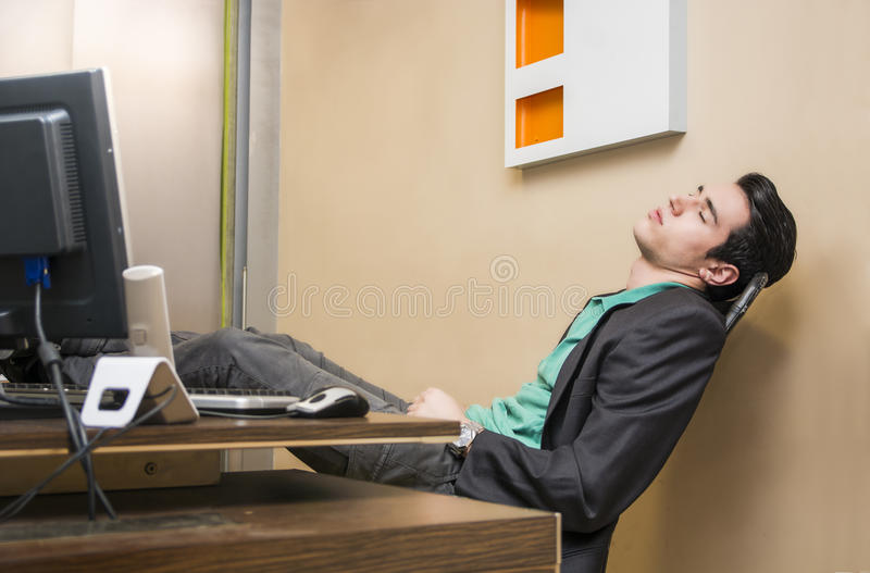 Overworked, tired young businessman sleeping. At his desk in office, in front of computer stock images