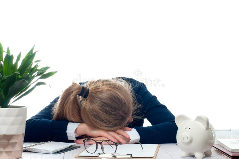 Overworked and tired young woman sleeping on desk at office. Too much work stock photo