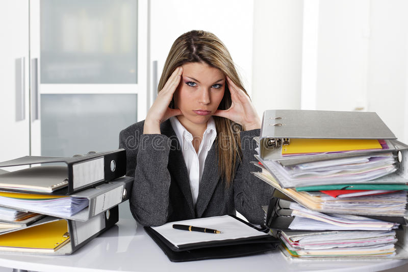 Overworked woman. Overworked blond woman in office stock photography