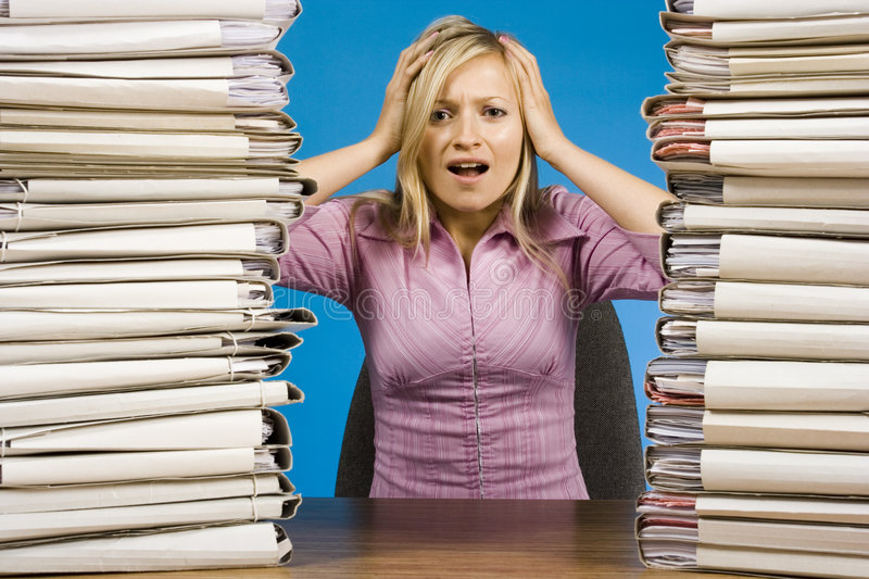 Overworked woman at the office desk royalty free stock photo