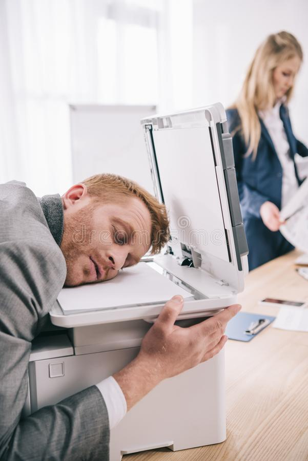 overworked young businessman sleeping with head on copier royalty free stock images