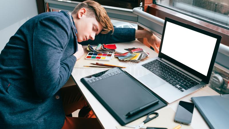 Overworking exhausted designer sleep work planning. Overworking fatigue. Exhausted tired designer sleeping on the desk in his workplace. Inefficient work royalty free stock photos