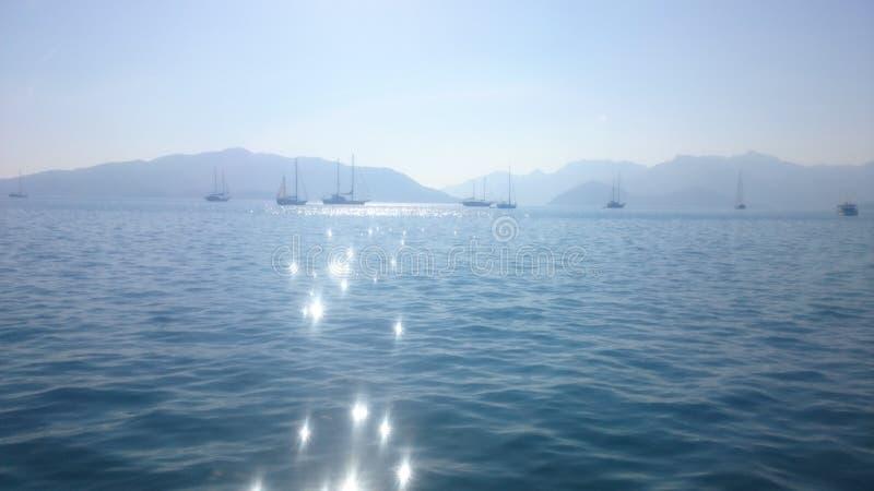 Overzees, berg en zon stock afbeelding