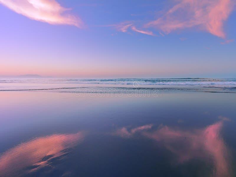 Overzees bij zonsondergang met wolkenbezinningen over zand royalty-vrije stock afbeeldingen