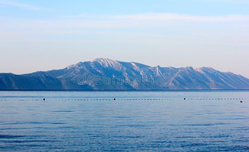 Overzees en bergen bij zonsopgang stock afbeelding