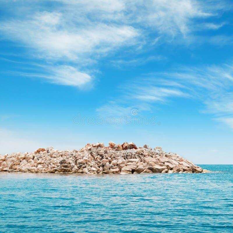 overzees en het rotsachtige eiland stock foto's