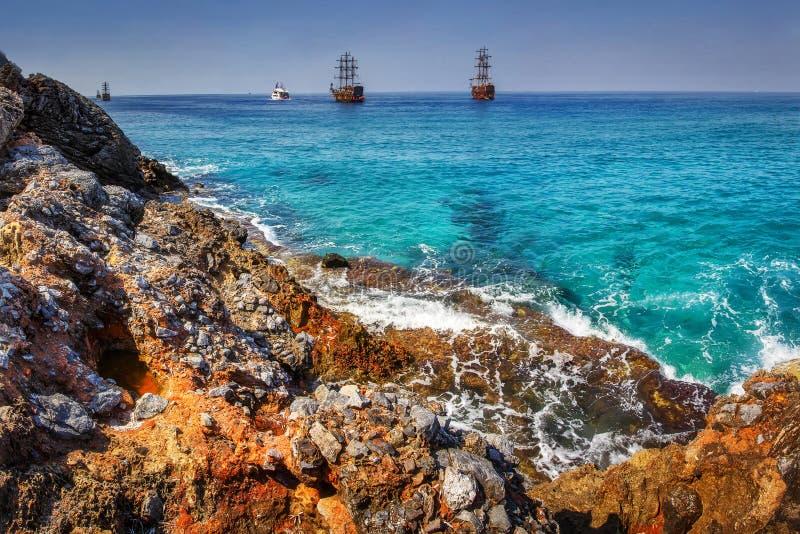 Overzees en rotsenlandschap in tropische baai Golven op Rocky Beach Overzees en bergen met schepen op horizon op de zomer zonnige royalty-vrije stock afbeeldingen