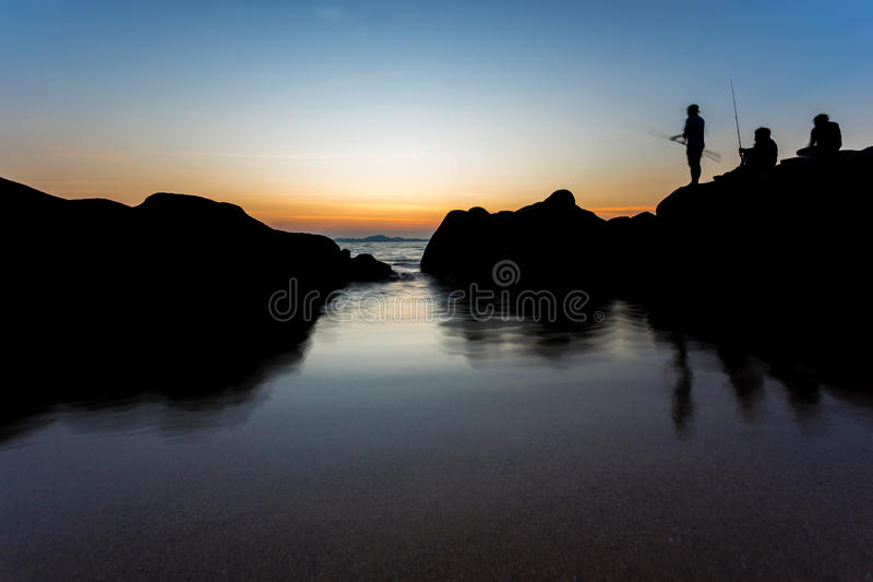 Overzees landschap en visserstribune op rots bij strand met zonsondergang t royalty-vrije stock fotografie