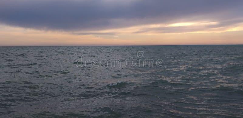 Overzees landschap met wolken en golven stock foto's