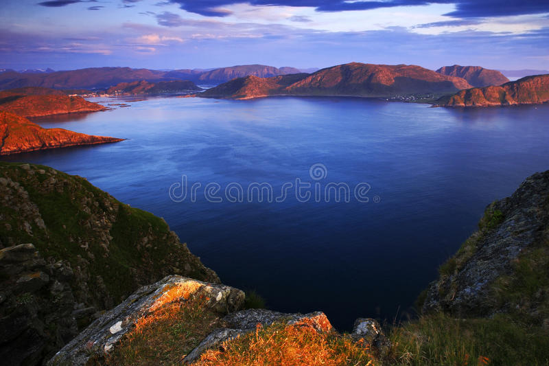Overzees landschap in Noorwegen Evenig roze licht op de oceaankust Rotsachtige kosten in de de zomernacht Waterspiegel met mooie  stock afbeelding
