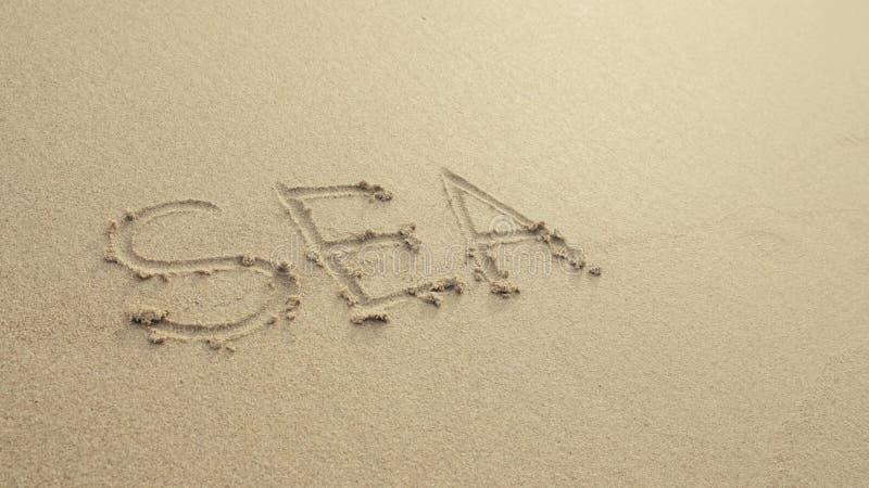 OVERZEES met hart op het strandzand wordt door golven altijd wordt gewassen geschreven die stock foto's