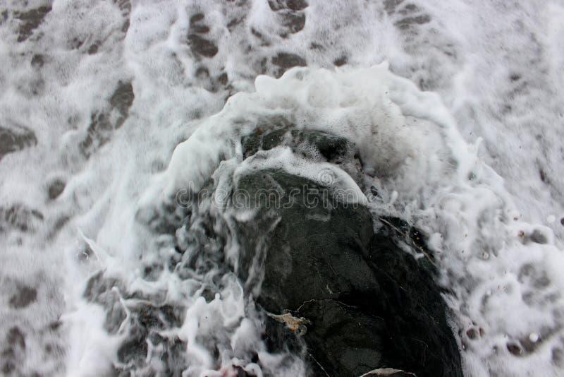 Overzees schuim rond de steen stock foto