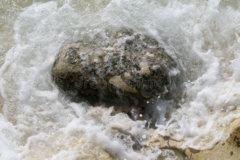 Overzees schuim rond een grote steen stock afbeelding