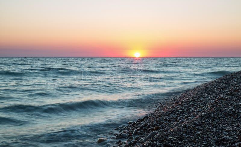 Overzees strand bij zonsondergang stock foto's