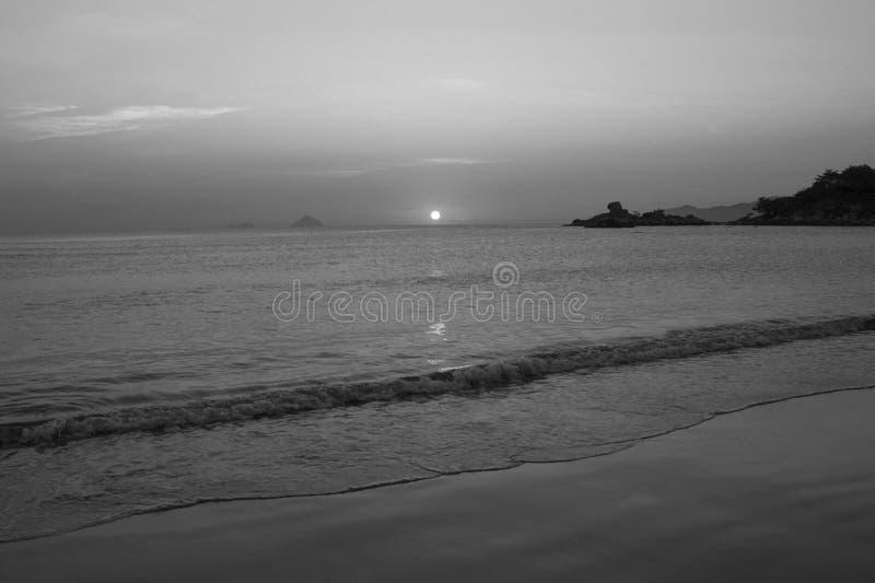 Overzees strand bij zonsopgang en zonsondergang stock foto's