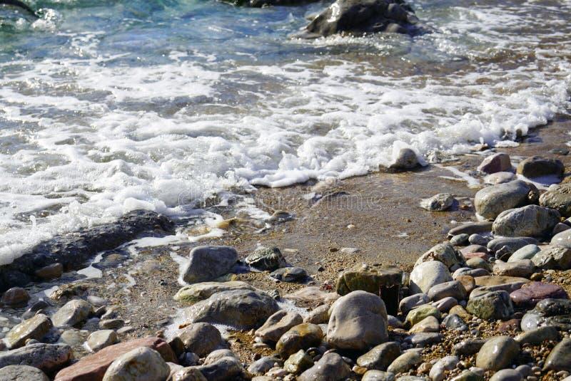 Overzees strand en een kleine golf stock foto