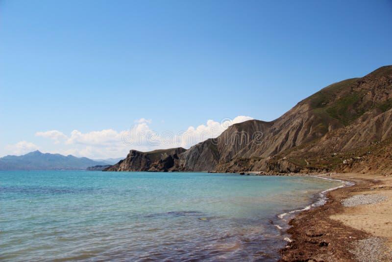 Overzees strand met bergen stock afbeeldingen