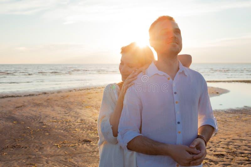 Overzees van Kalmte Een gelukkig paar omhelst teder tegen de het plaatsen zon De vrouw achter de man royalty-vrije stock afbeeldingen
