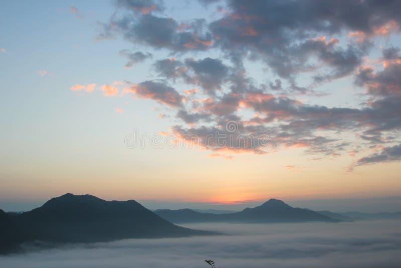 Overzees van mist en zonsondergang op berg stock afbeeldingen
