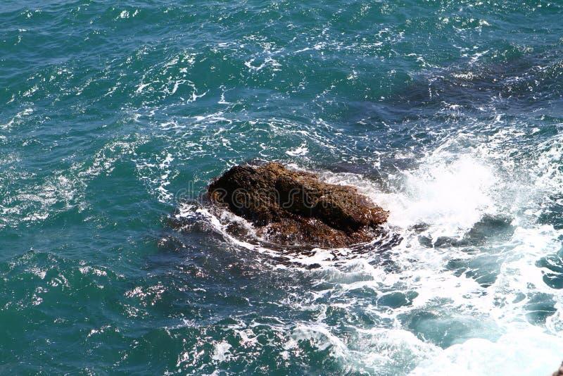 Overzees van Nice steenachtig helder blauw strand met grote stenen op een de zomerdag, foto van aard stock afbeelding