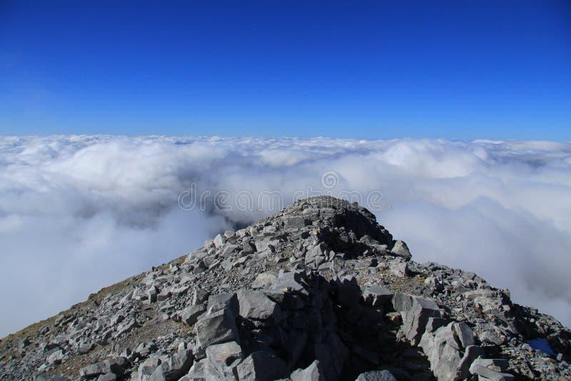 Overzees van wolken die bergen behandelen onder een zonnige hemel royalty-vrije stock fotografie