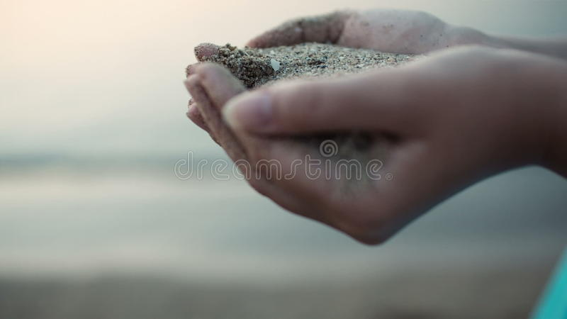 Overzees zand die de handen van een vrouw doornemen