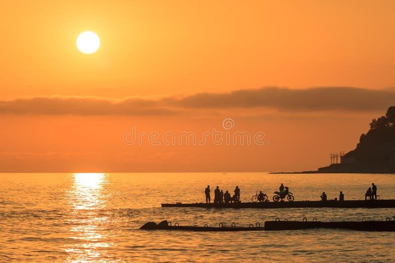 Overzees zonsondergang toneelzeegezicht met verre silhouetten van mensen royalty-vrije stock foto's