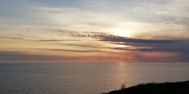 Overzees zonsonderganglandschap De het plaatsen zon glanst door ongebruikelijke wolken Mooie natuurlijke achtergrond stock afbeelding