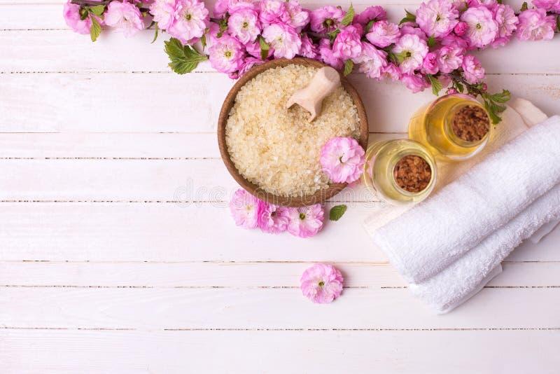 Overzees zout in kom, flessen met aromaoliën, handdoeken en roze flowe stock foto's