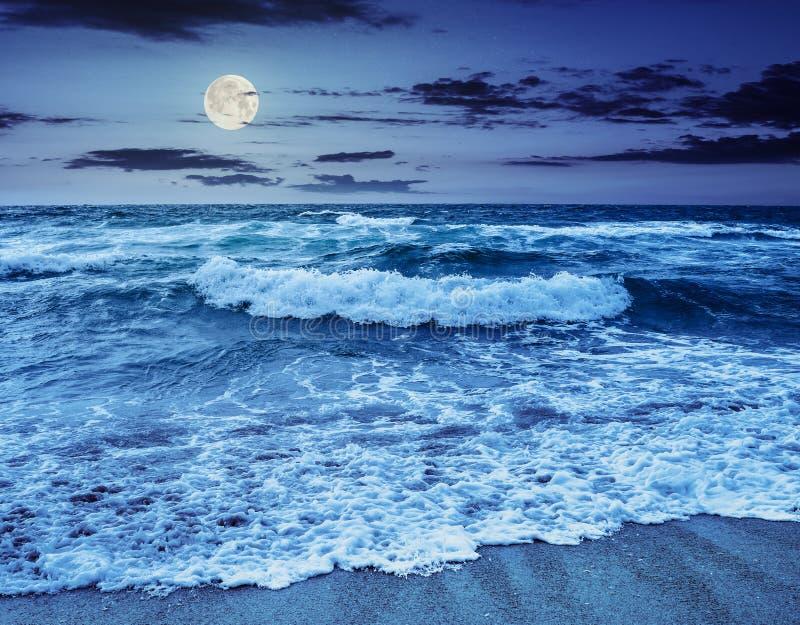 Overzeese †golven ‹die †‹op zandig strand bij nacht verpletteren royalty-vrije stock afbeelding