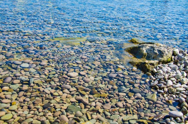 Overzeese achtergrond, rimpelingsoppervlakte van transparant water stock foto's