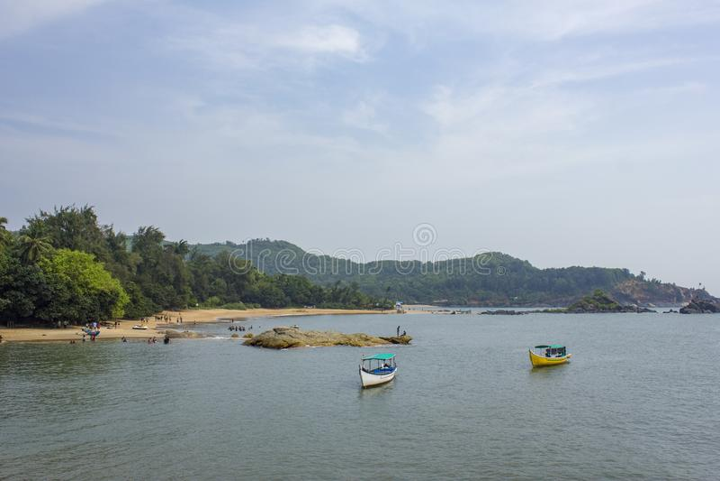 Overzeese baai met plezierboten op het water, tegen de achtergrond van het groene bos op het het zandige strand en mensen rusten stock afbeelding