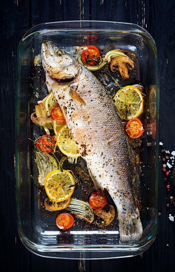 Overzeese baarzen op bakselschotel Ingrediënten voor het koken, gebakken grill, royalty-vrije stock afbeeldingen