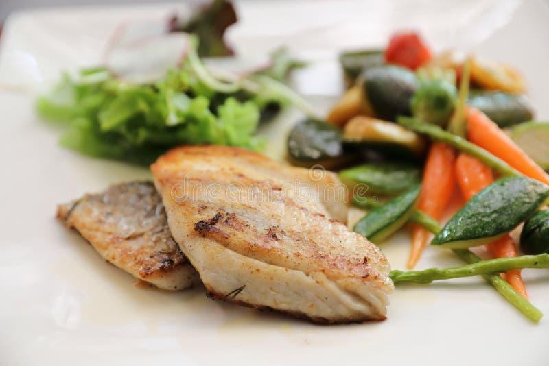 Overzeese baarzenfilet met geroosterde groenten en salade op houten lijst royalty-vrije stock afbeeldingen