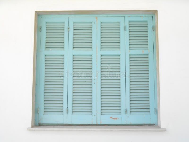 overzeese blauwe zonneblinden op venster met de lichte muren van de huidtoon stock afbeelding
