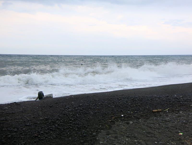 Overzeese branding en golven die op het strand verpletteren stock afbeelding