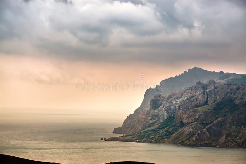Overzeese de lentezonsondergang over de bergen royalty-vrije stock fotografie