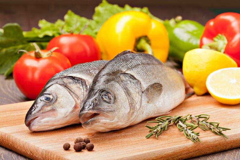 Overzeese die baarzen aan het koken op de achtergrond van groenten worden voorbereid en stock afbeeldingen