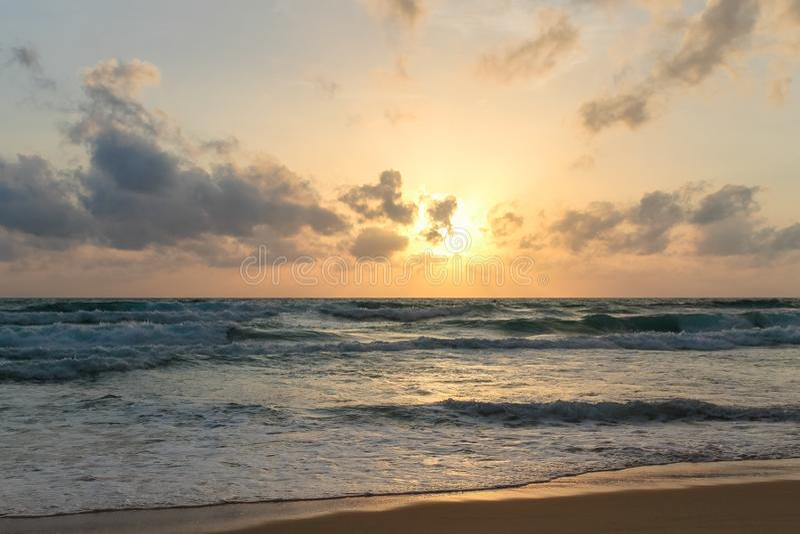 Overzeese die golven tegen een achtergrond van een zonsondergang door wolken wordt gesloten stock afbeelding